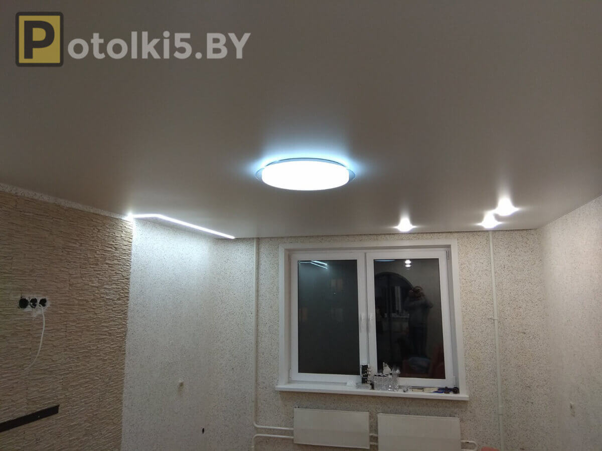 Сатиновый потолок в комплексе с эксклюзивным полотном (полоски); в качестве освещения парящие линии, люстра, светильники; скрытый карниз